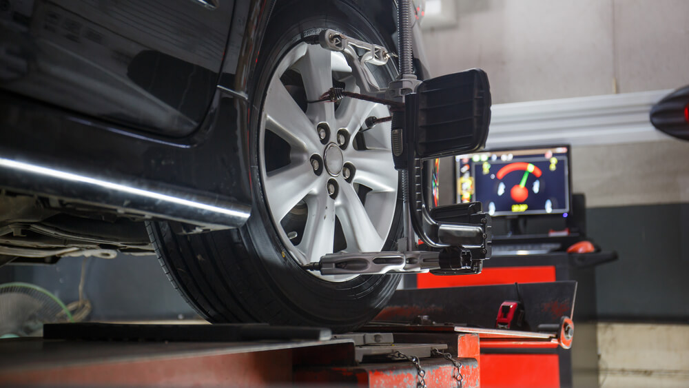 Wheel alignment device on wheel and computer screen in background